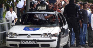 Policemen and soccer fans stand behind a damaged vehicle during clashes in Siroki Brijeg
