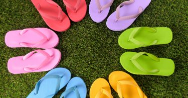 Multicolor circle of flip flops on grass.