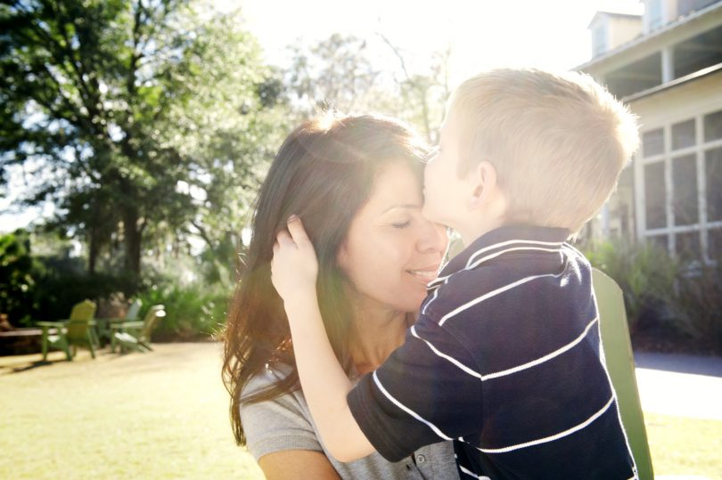 Son kissing mother on forehead
